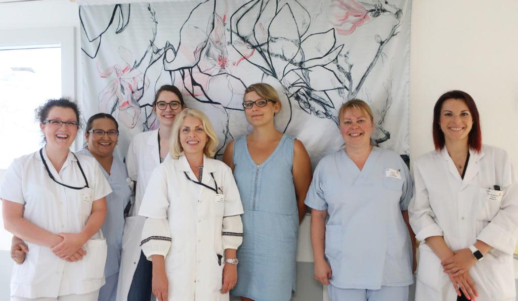 Portrait de l'équipe d'oncologie avec l'artiste et son tableau de fleurs dans les couloirs de l'hôpital.